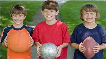 Three boys, each holding a different sport's ball.